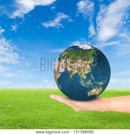Green Earth concepthand holding earth against green field and blue sky background.Elements of this image furnished by NASA