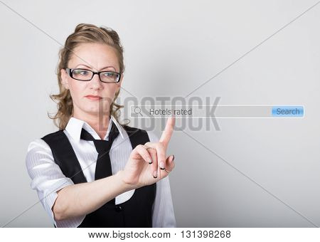 Hotels rated written in search bar on virtual screen. technology, internet and networking concept. Internet technologies in business and home. woman in business suit and tie, presses a finger on a virtual screen.