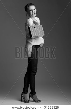 Smiling Elegant Woman With Shopping Bag Against Grey Background