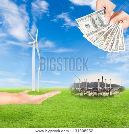Carbon credits concepthand holding wind turbine and US Dollars banknote with oil refinery plant against green field and blue sky background