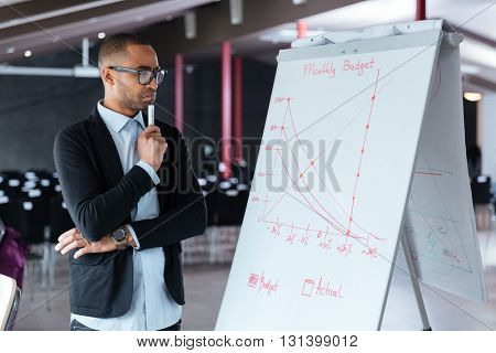 Pensive businessman thinking about presentation using flipchart