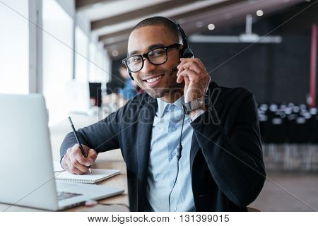 Stylish smart businessman using headphones during his work at the office