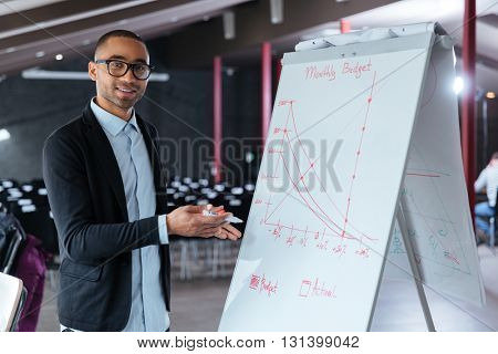Smart stylish businessman presenting something on flip chart