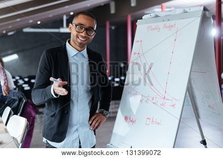 Handsome businessman making presentation using flipchart in the office