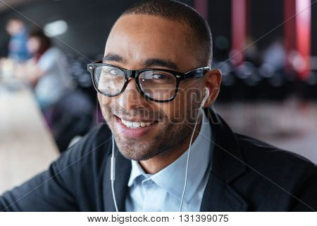 Close-up portrait of a smiling businessman wearing earphones at the office