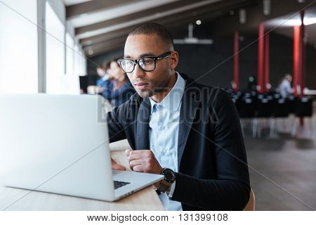 Young handsome businessman working with laptop in the office