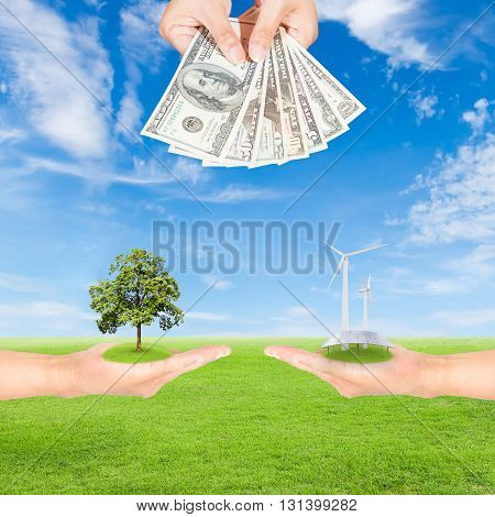 Carbon credits concepthand holding wind turbine solar panels tree and US Dollars banknote against green field and blue sky background