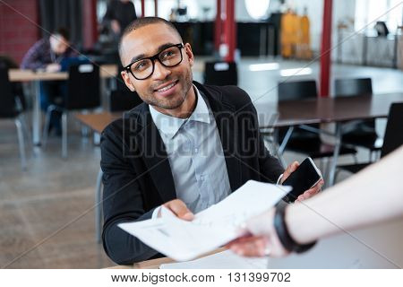 Young businessman giving papers to someone in the office
