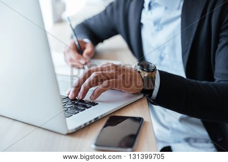 Close-up portrait of multitasking mans hands using laptop and writing notes