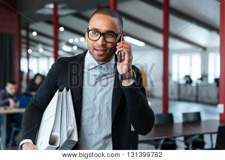 Young bisnessman carrying folders and talking on the phone in the office