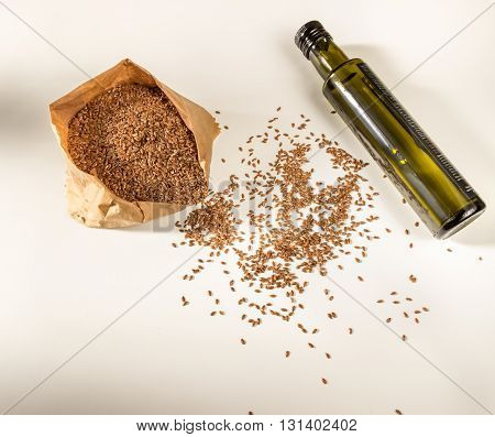 Flaxseed and flaxseed oil bottle on a light background