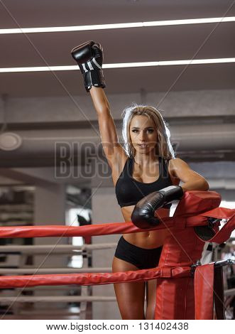 Young pretty boxer woman standing on ring with raised up hand