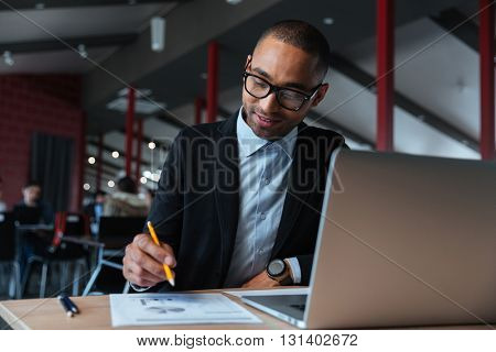 Young businessman working with laptop and writing notes in the office