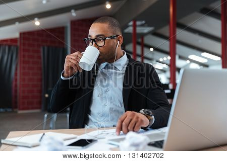 Businessman drinking and listening to music in the office with laptop