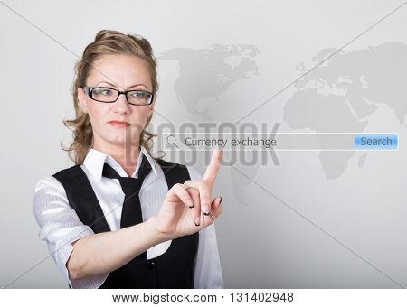currency exchange written in search bar on virtual screen. technology, internet and networking concept. Internet technologies in business and home. woman in business suit and tie, presses a finger on a virtual screen.