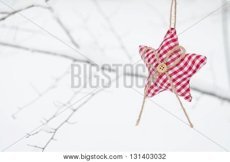 textile red star on snowy tree brunch in winter