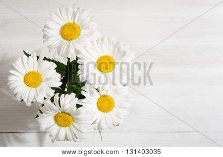 bouquet of daisies on light wooden table