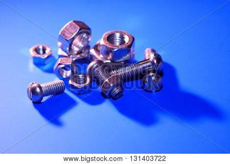 Set of metal nuts on blue background with shadow
