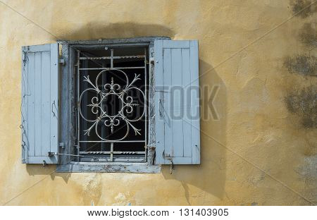 Blue iron window on a worn stucco wall. Antique european style.