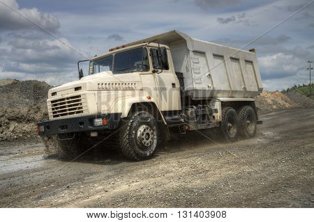 Poltava Region Ukraine - June 26 2010: Dump truck driving along the iron ore opencast with splashes of mud