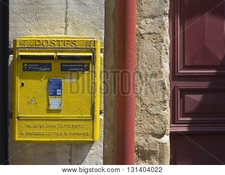 Saint Jean de Luz - Ciboure France - May 21 2016: French yellow metal mailboxes on stone wall in a street of Aquitaine. France.