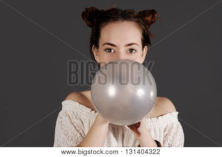 Funny young hipster woman is blowing a balloon. Studio shot with dark background.