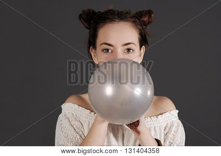 Funny young hipster woman is blowing a  grey balloon. Studio shot with dark background.