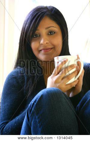 Joven mujer asiática atractiva con taza de bebida caliente