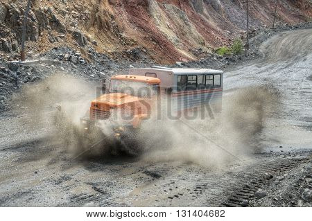 Poltava Region Ukraine - June 26 2010: Mining crew bussplashes driving at high speed along the iron ore opencast with mud splashes