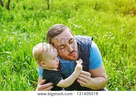 father and sons relationship, playing with dandelions in the Park