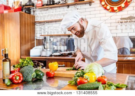 Cheerful handsome chef cook making vegetable salad on the kitchen