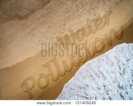 Water Pollution written on the beach