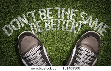 Top View of Sneakers on the grass with the text: Don't Be The Same Be Better