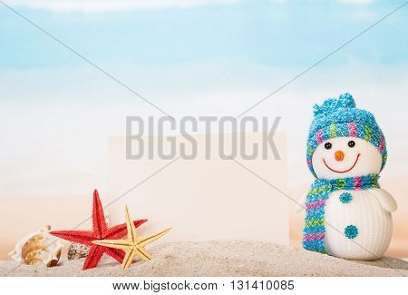 Blank card, sea shells, stars and snowman in the sand.