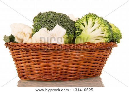 Inflorescences of broccoli and cauliflower in a wicker basket isolated on white background.