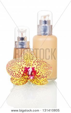 Cosmetic liquid foundation and orchid flower isolated on white background.