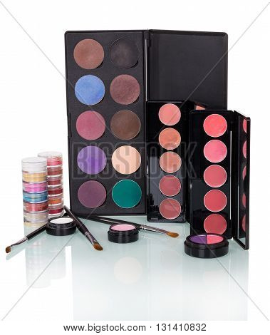 Set of professional makeup: eye shadow, blush, lip gloss and brushes isolated on a white background.
