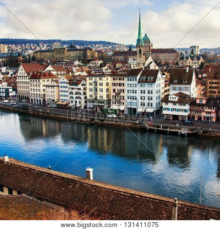 ZURICH, SWITZERLAND - FEBRUARY 27, 2014: Aerial view of old buildings in the city center of with Limmat river. Popular restaurants, cafes and shops. Car traffic and cloudy sky