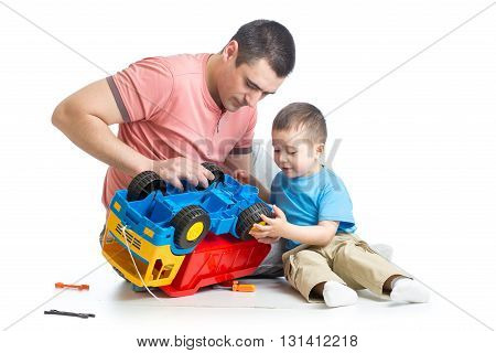 kid boy and his father fixing toy trunk