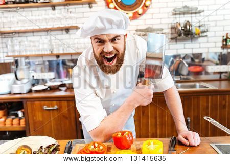 Angry bearded chef cook holding meat cleaver knife and shouting on the kitchen