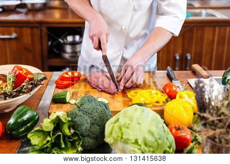 Professional chef cook standing and cutting uncooked meat and fresh vegetables on the kitchen