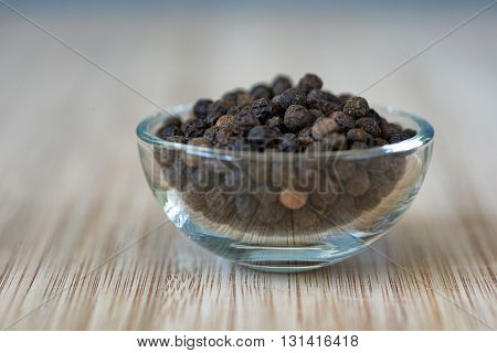 bowl full of black pepper grains on a bamboo board