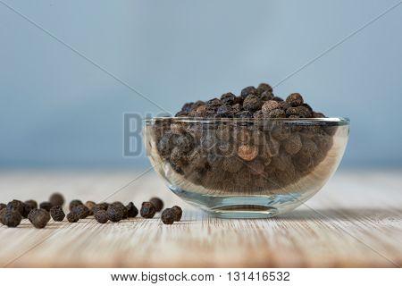 bowl full of black pepper grains on a bamboo board