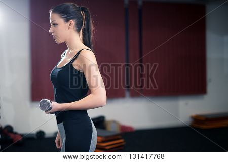 Woman doing exercises with dumbbells in the gym.