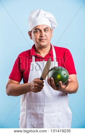 Indian male chef holding knife in one hand and water melon fruit in other hand, asian male chef posing with big knife and watermelon, isolated over blue background