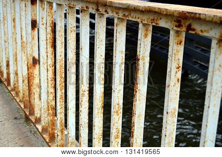 rusted white handrail of a bridge at the water