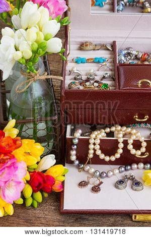 view of Jewellery in treasure box with fresh fresia flowers