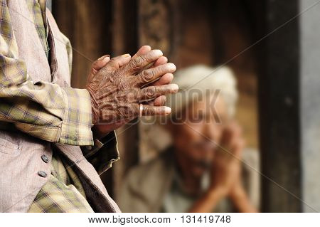 Hands of old buddhist praying to Buddha in a temple in Kathmandu
