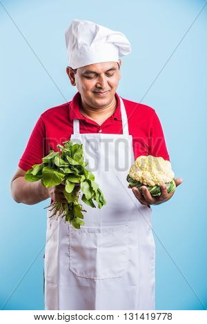 indian male chef holding fresh Cauliflower and spinach leaves, standing isolated over blue background, asian male chef holding fresh vegetables