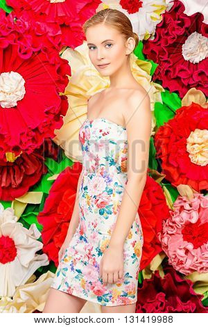 Beautiful tender woman in light summer dress posing by a big bright flowers. Fashion. Cosmetics. Spring, summer concept.